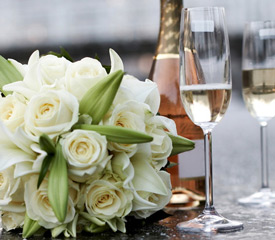 A wedding bouquet next to a bottle of champagne and two flutes
