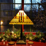 A festive lamp lights nearby wreaths