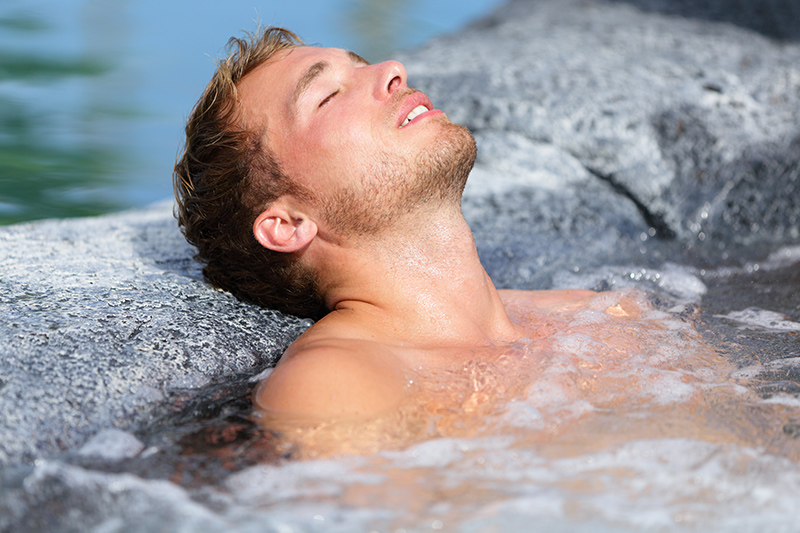 Man Relaxing in Hot Springs Tub