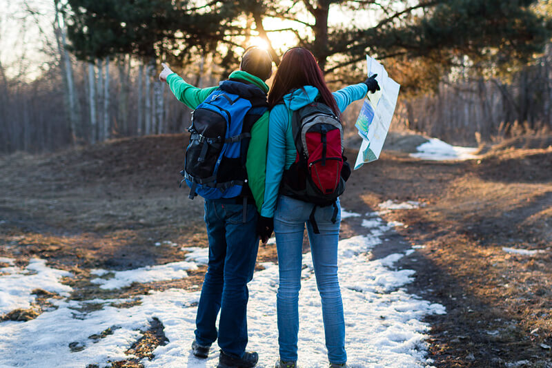 COuple with backpacks hiking on snow covered ground in Santa Fe