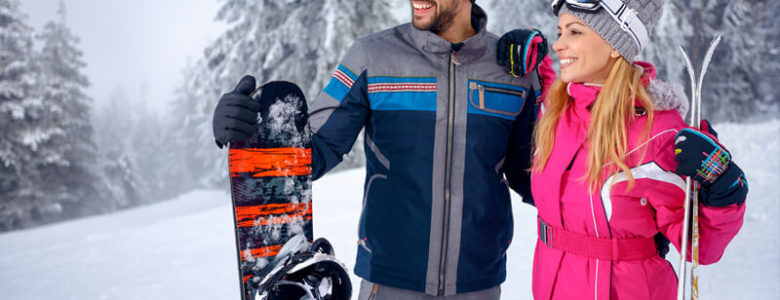 Cute yong couple in ski gear holding a snowboard and skis surrounded by snow in Northern New Mexico