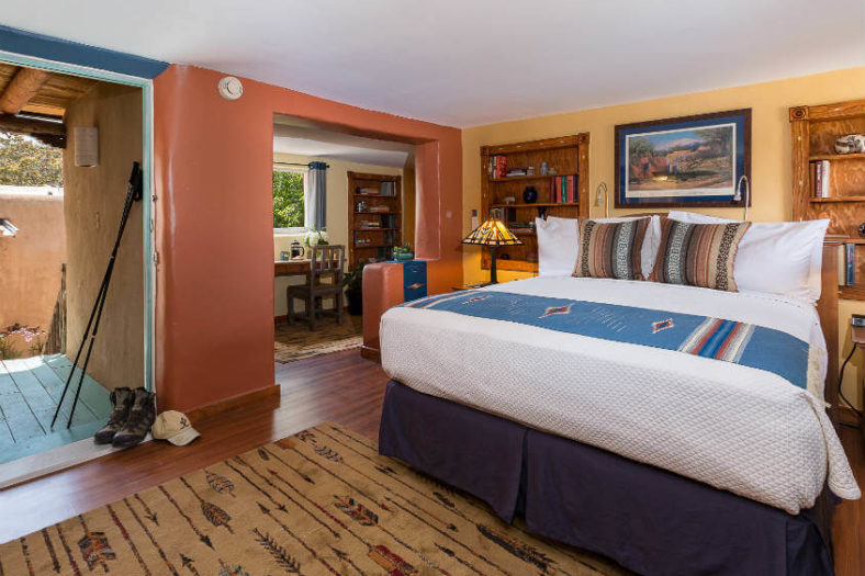 queen sized bed, office desk and hiking boots in DH Lawrence guest room