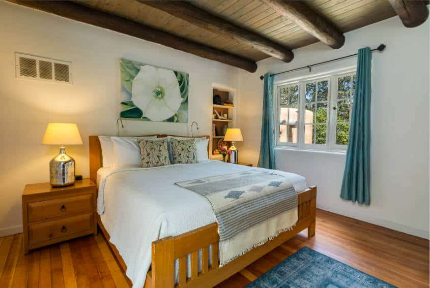 Georgia O'Keeffe guest room bed with night stands and window views to garden