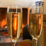 Champagne flutes sparkling in front of burning fire in fireplace