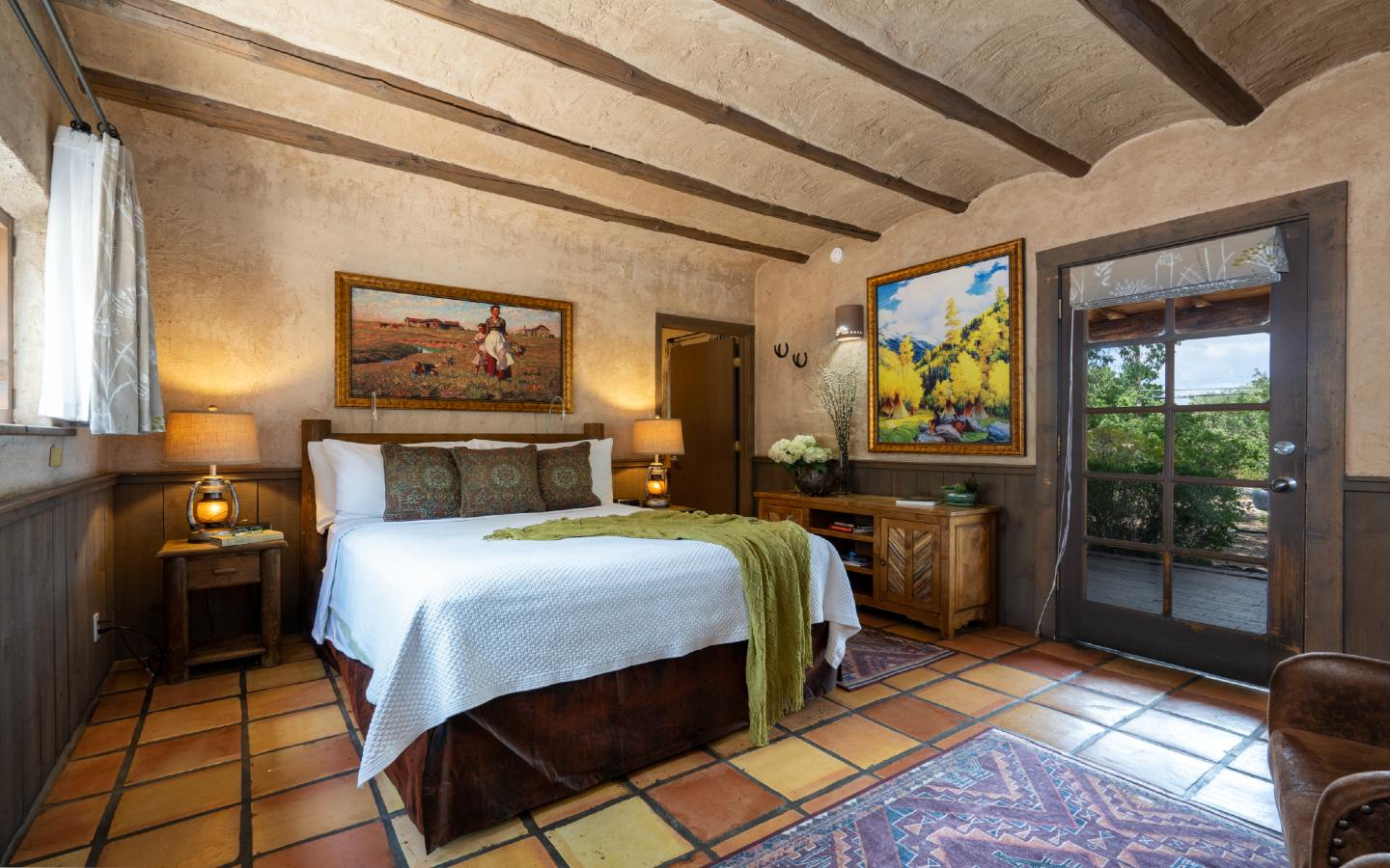Queen sized bed, credenza, beautiful artwork and door leading to the garden in the Willa Cather guest Room