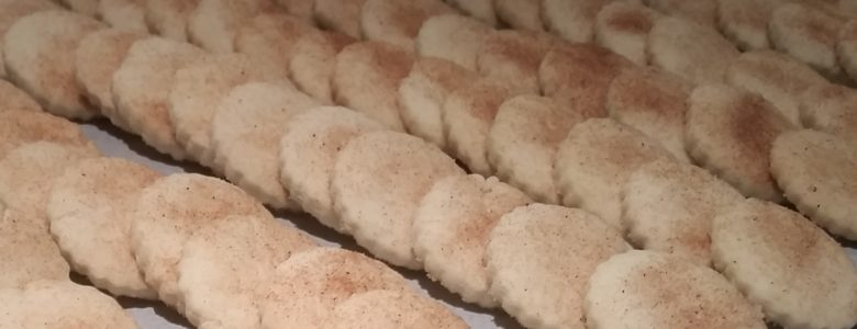 Rows of fresh baked bizcochito cookies on a baking sheet