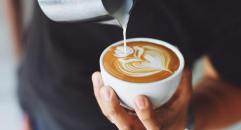 Barista pouring cream into cup for a decorative latte