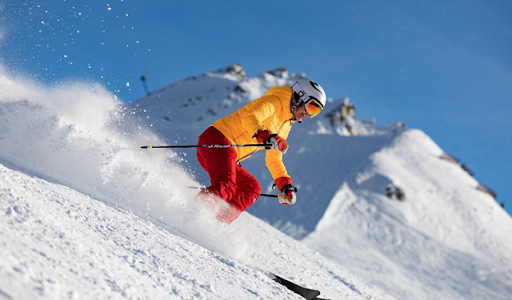 Downhill skier in bright clothng with snow flying behind