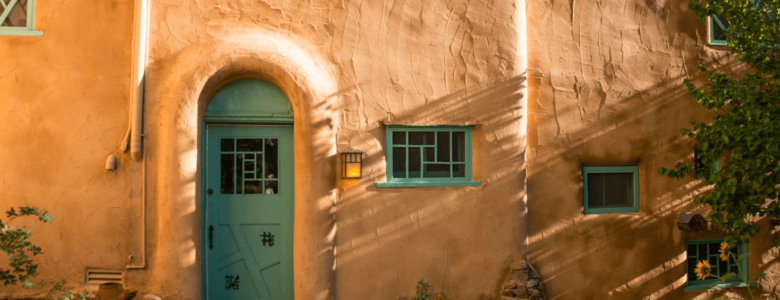 Exterior view of Inn of the Turquoise Bear with clay colored adobe and turquoise trim and front door