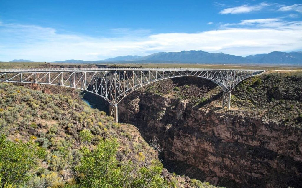 Stunning bridge over two mountains on the way to taos nm amidst blue skies